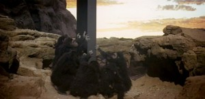 Scene from 2001 with primitive humanoids pawing at monolith.